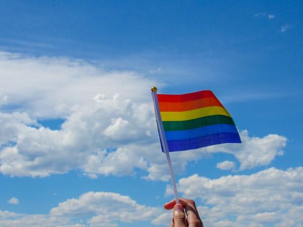rainbow flag waving against a blue sky