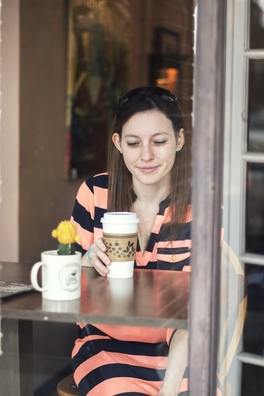 Woman sat in a cafe window drinking out of a coffee cup