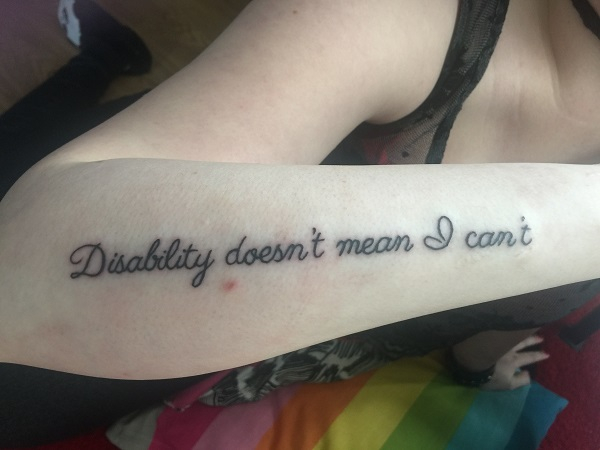 tattoo on the forearm of a woman that says disability doesnt mean I cant in a swirly font