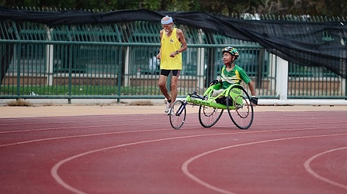 Wheelchair athlete and man jogging on stadium circuit