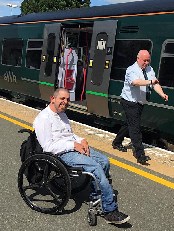 A man Richard in a wheelchair waiting at a train station platform