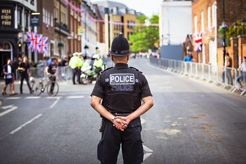 A police man looking down a high street