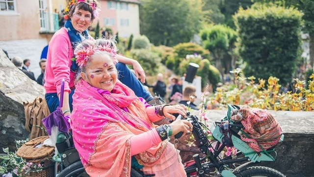 female wheelchair user at festival wearing lots of flowers