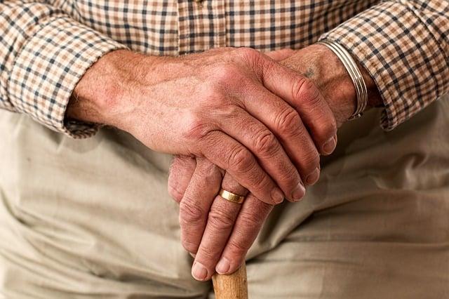 older mans hands holding a walking stick
