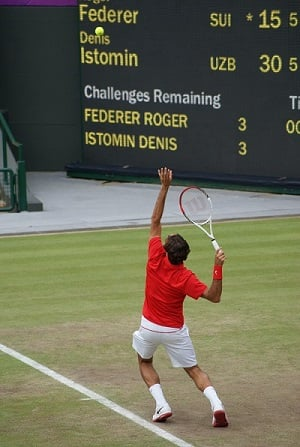 Male tennis player serving with ball in the air and racket ready to hit