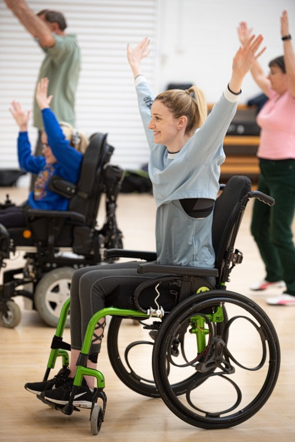 Kate smiling in gym wear with her arms in the air She is in a dance studio and sat in her wheelchair