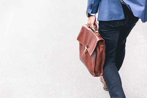 briefcase in the hand of a man with a blue suit on