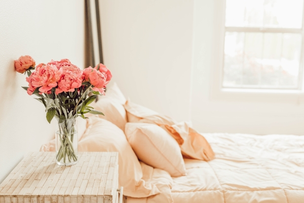a made bed with pink flowers in a vase on the bed side table