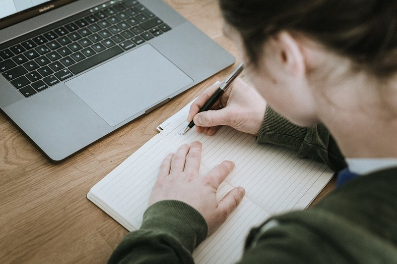person writing with pen on blank paper positioned in front of laptop