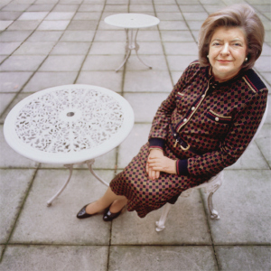 Verite sitting on a chair smiling at the camera, next to a garden table