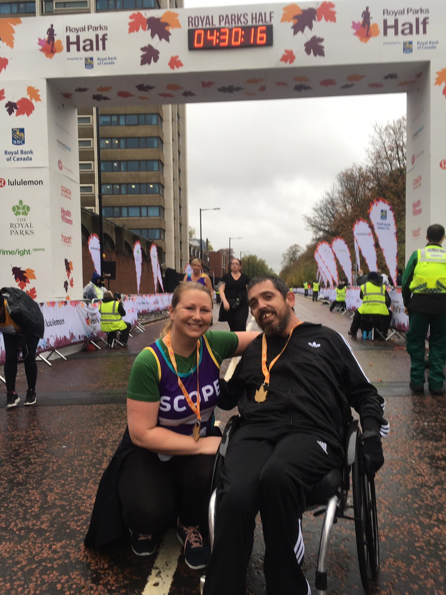 Man in a wheelchair and a woman with a Scope t-shirt on posing for a picture by the finish line