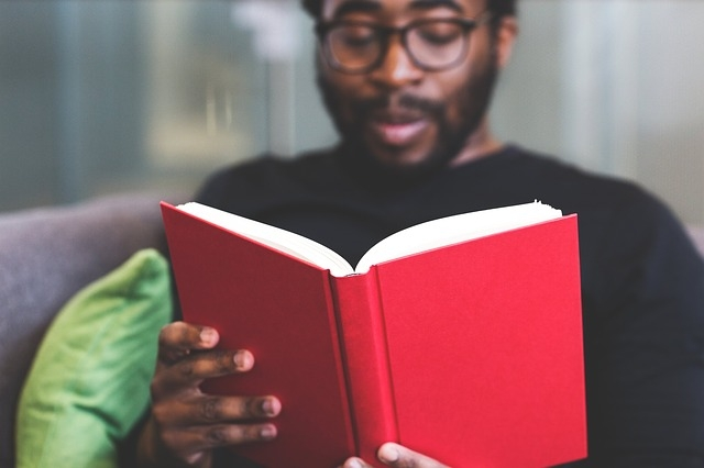 male student reading a book