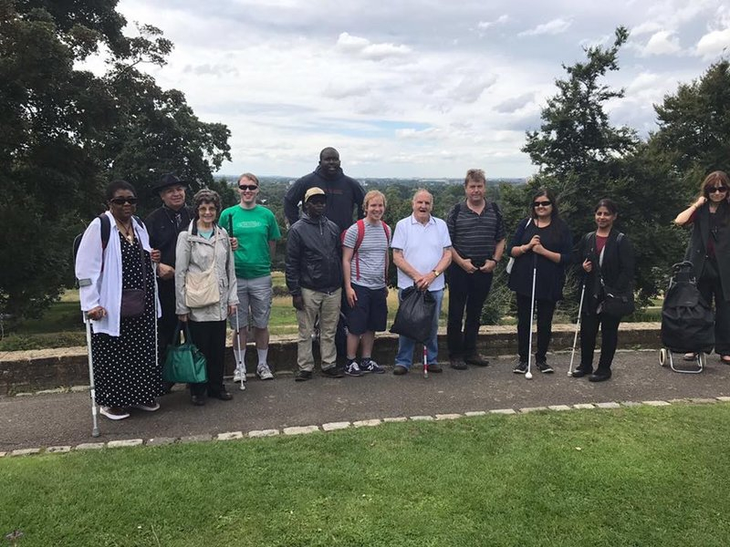 a group of a dozen visually impaired people standing up in a park surrounded by greenery and smiling