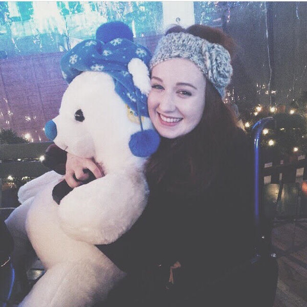 girl sat in wheelchair smiling and holding a huge white teddy bear in front of a background of Christmas lights