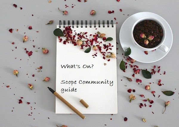 pad of paper and a pen with rose petals and a cup of coffee on the pad it says whats on scope community guide