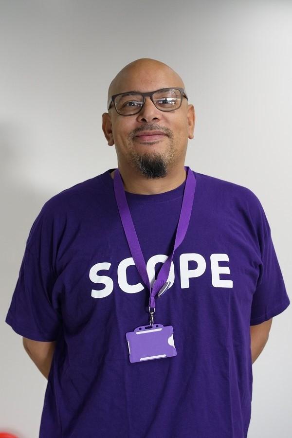 man smiling to camera wearing a purple Scope Tshirt