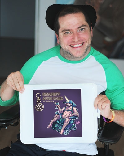 Andrew smiling at camera holding up a piece of artwork which says Disability After Dark