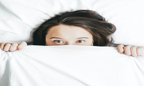 woman laid in bed with head peeping over top of blankets