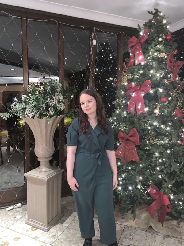 Charli is stood in front of a decorated christmas tree she is wearing a green jumpsuit