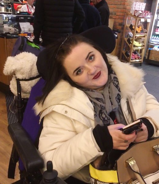 daniella in powerchair in a shop holding phone and looking at camera