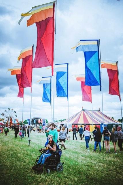 wheelchair user festival goer under some flags