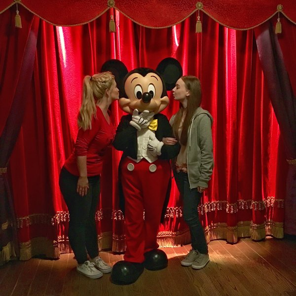 Two young adult females stood up either side of Mickey Mouse holding his arms and pretending to kiss his cheeks