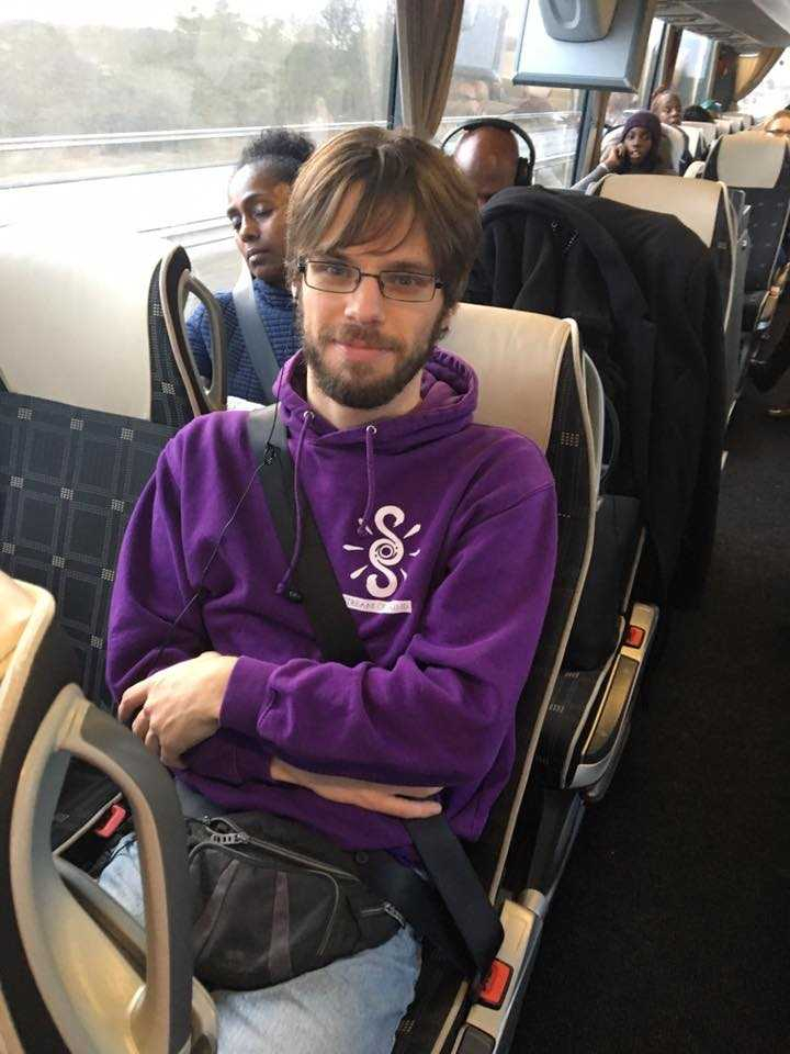man with beard brown hair and glasses wearing a purple jumper sat on a bus
