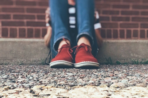 Young person leaning against a wall - close up on their red shoes and blue jeans