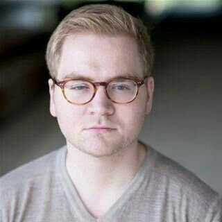 professional headshot of a male with light hair and glasses wearing a grey shirt looking directly at the camera