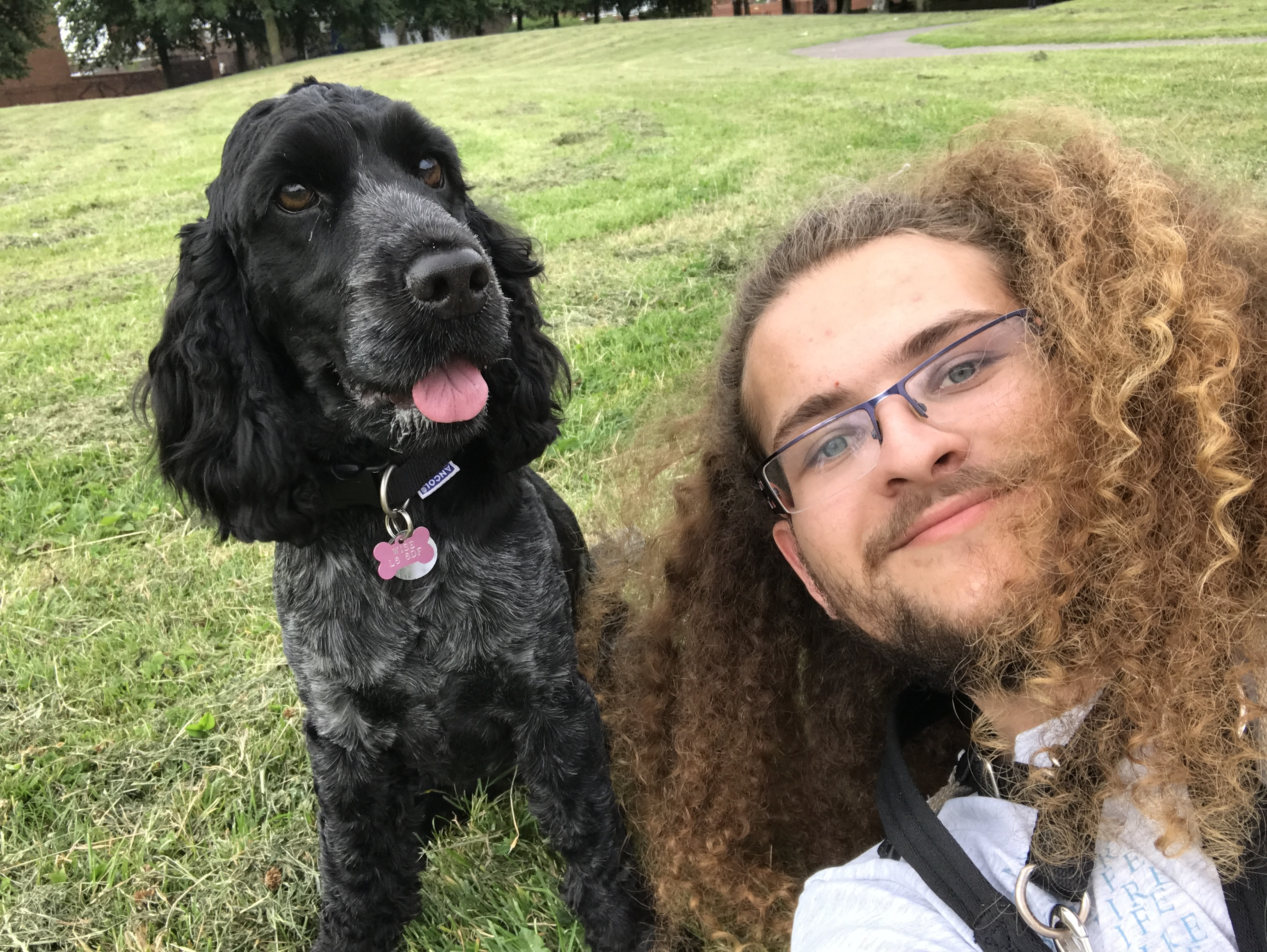 Deaf man, with glasses and long hair, with black dog