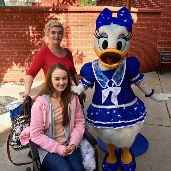 young adult female wheelchair user and friend posing for a picture with Daisy Duck in Disneyland Paris