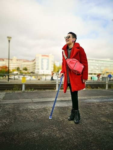 Imogen wearing a bright red coat and a beaming smiling while standing with a walking stick