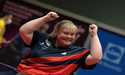 Sue smiling celebrating success with her arms raised