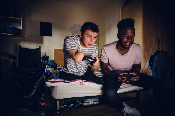 disabled young man playing a video game with his friend