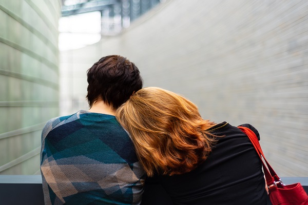 A woman leaning her head against a mans shoulder as they look outwards with their backs to the camera