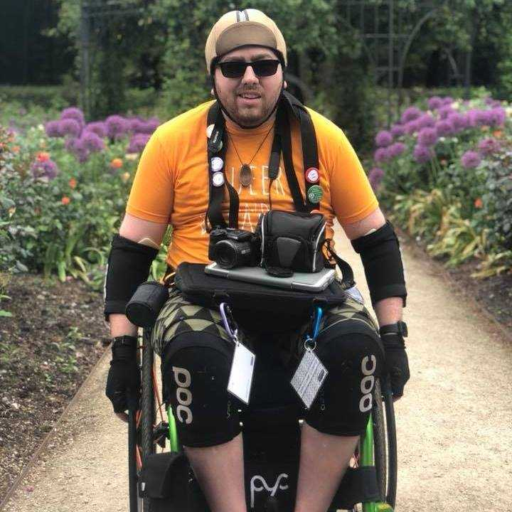 oliver in wheelchair wearing sport clothing and orange top with photography equipment on his lap