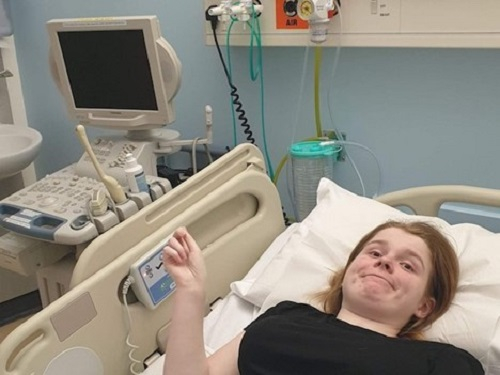 Ami laid in hospital looking tired and frustrated with an ultrasound machine stood at the side of her bed