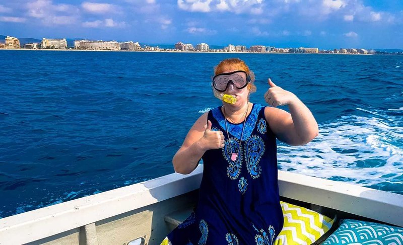 jenni stood with thumbs up wearing a scuba diving mask with blue sea in background