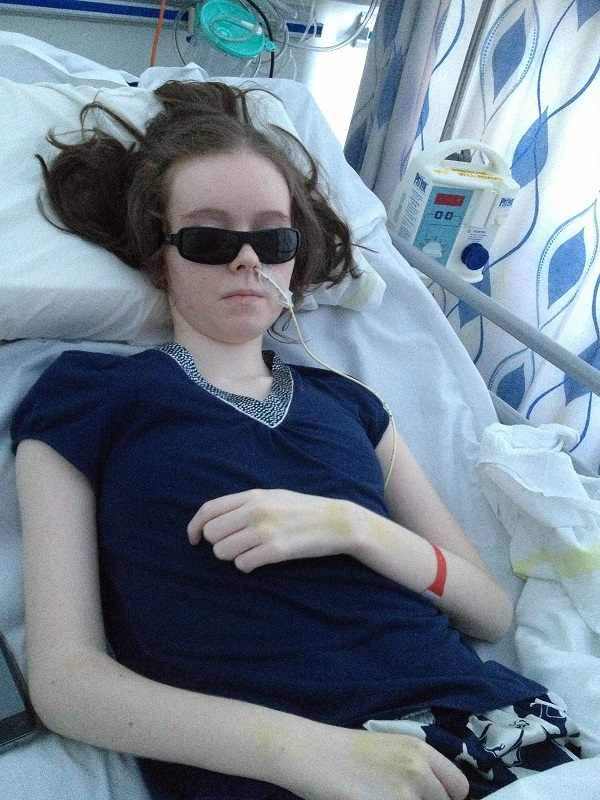 A young woman wearing dark glasses while laid in a hospital bed