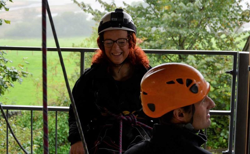 red haired woman with glasses wearing a helmet and abseiling gear smiling at camera