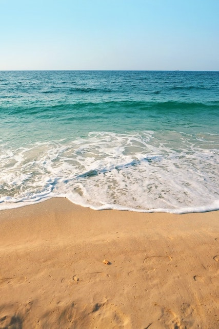 Photograph of clear blue sea and frothy tide coming inwards