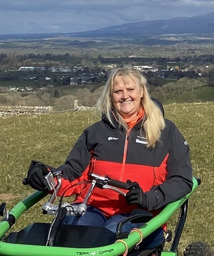 Debbie smiling sat in her wheelchair with green hills and countryside in the background