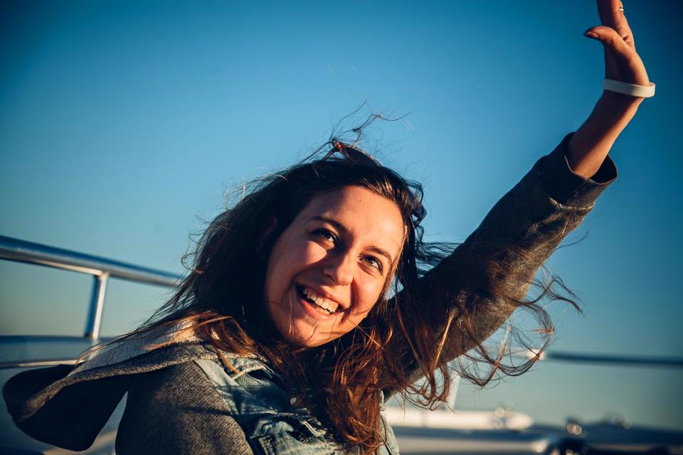 vix smiling with arm raised in the air with blue sky in the background