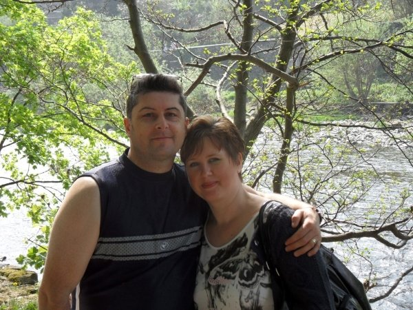 Victoria and her husband stood in woods