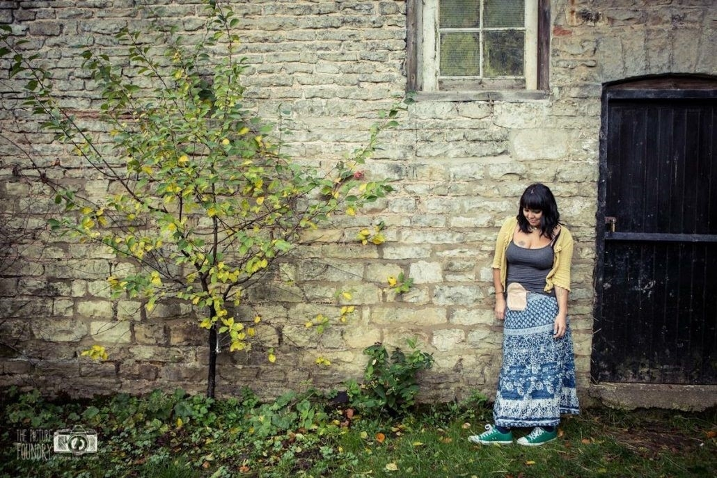 woman stood in countryside showing ostomy bag