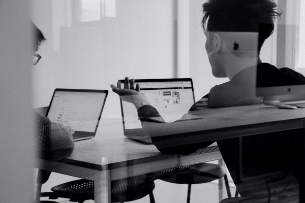 Black and white photo of two people sat in a meeting with their laptops open