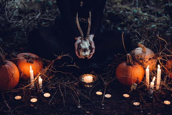 Hands holding a skull with pumpkins either side and lit candles