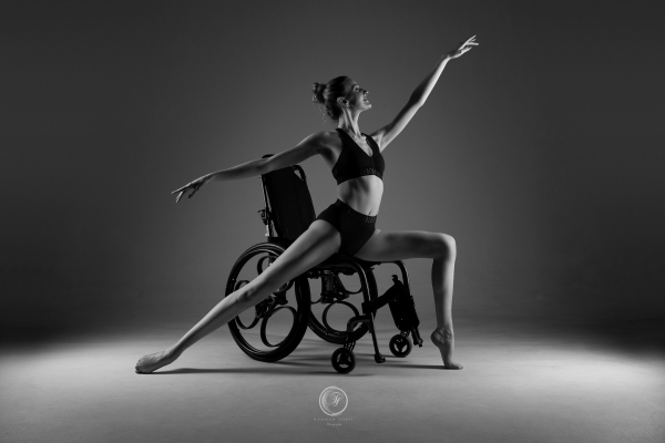 Black and white of Kate stood in a ballet position extending her arms and legs Her wheelchair is behind her