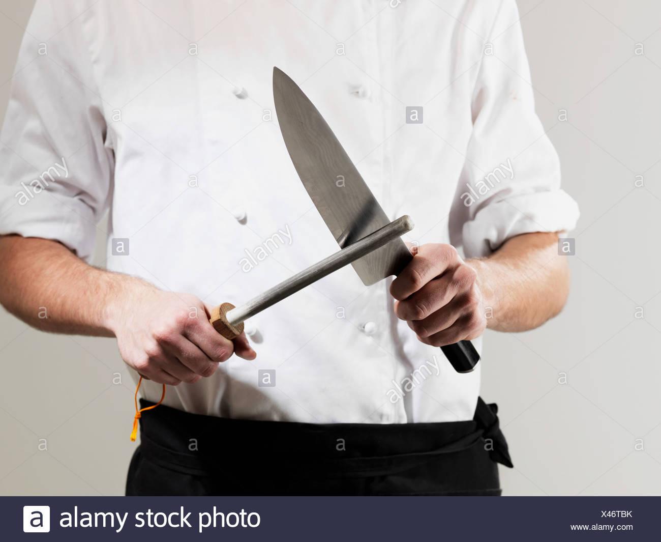 chef-sharpening-knife-against-white-background-X46TBK.jpg