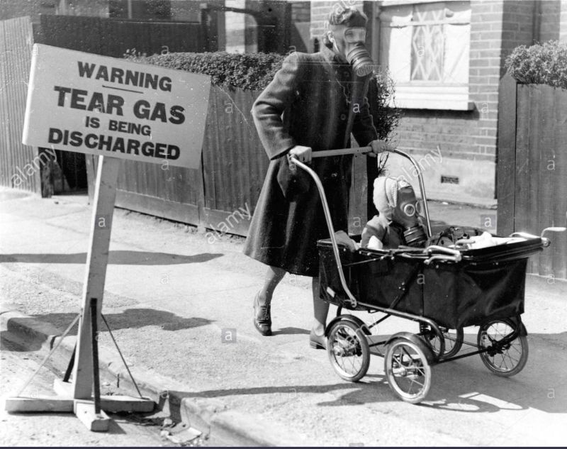 a-mother-pushes-her-baby-in-a-stroller-wearing-gas-masks-BEDKE0.jpg